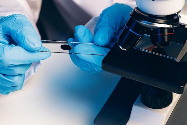 Handen van een laboratoriumarbeider die bloedonderzoek doen