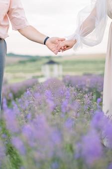 Handen van een liefdevol stel, man en vrouw, wandelend op een prachtig bloeiend lavendelveld