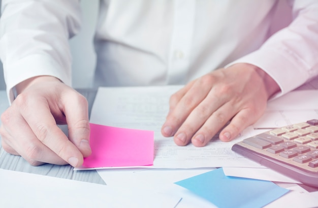 Handen van een man aan het werk met papieren