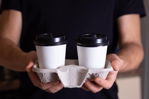 Handen van een man die aanbiedt om koffie in papieren bekers te nemen