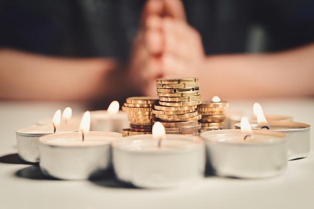 Handen van een man die bidt met een cirkel van brandende kaarsen met een stapel munten erin