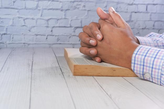 Handen van een man die bidt over een boek,