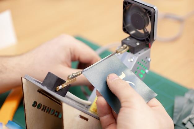 Handen van een man die de randen van labels en labels afsnijdt voor kleding op een elektrische touwsnijder met verwerking op hoge temperatuur