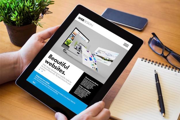 Handen van een man die een apparaat van de websitebouwer boven een houten werkruimtetafel houdt. alle schermafbeeldingen zijn verzonnen.
