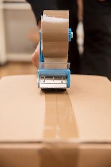 Handen van een man die een bandautomaat gebruikt om een verzenddoos te verzegelen