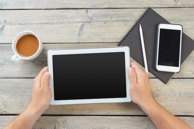 Handen van een man die een leeg tablet-apparaat vasthoudt boven een houten werkruimtetafel