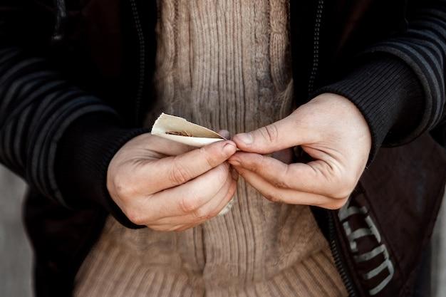 Handen van een man die een sigaret rolt.