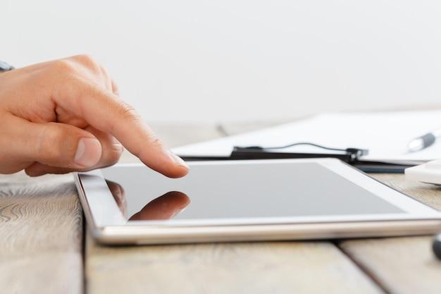 Handen van een man die een tablet vasthoudt boven een houten werkruimtetafel