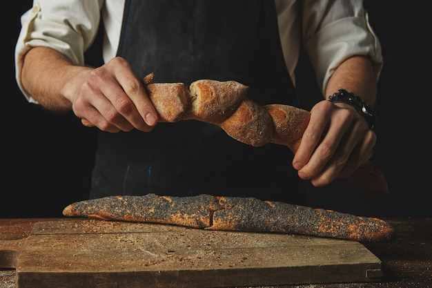 Handen van een man die stokbrood breekt en deelt
