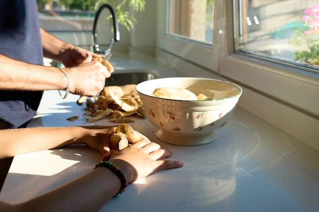 Handen van een man en een kind die aardappelen schillen in de keuken, geen gezichten te zien
