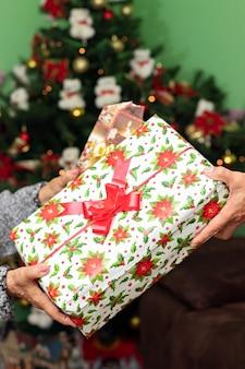 Handen van een man en een vrouw die elkaar kleine cadeautjes geven in kerstmis