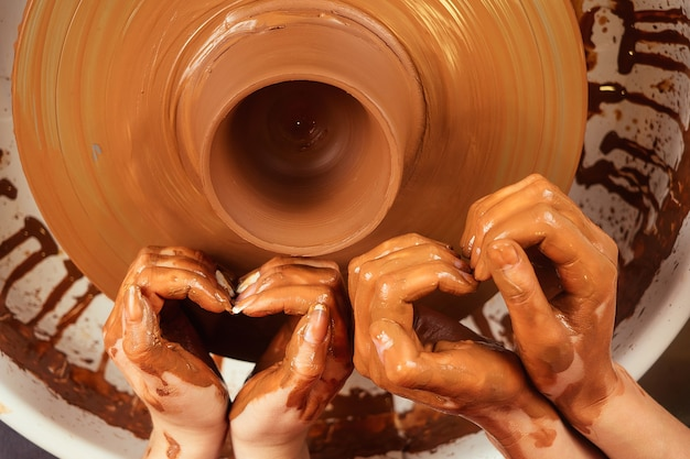 Handen van een man en een vrouw in de vorm van een hart in klei op een pottenbakkersschijf vormen een vaas. de pottenbakker werkt in een pottenbakkerij met klei. het concept van valentijnsdag en liefde in aardewerk
