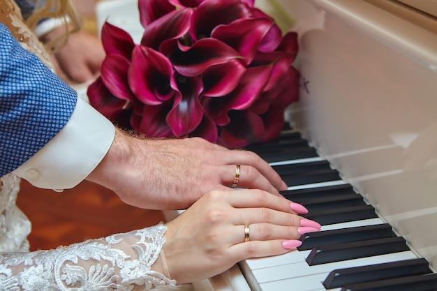 Handen van een man en een vrouw met trouwringen op de pianotoetsen