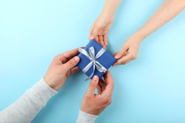 Handen van een man en kind met een geschenk bovenaanzicht