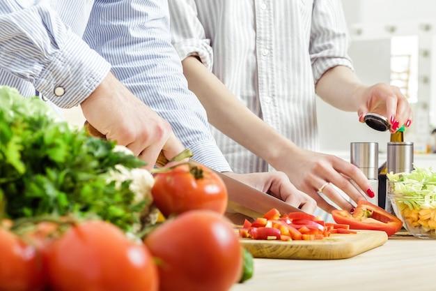 Handen van een man gehakte rode paprika voor salade op een bord. paar hakken van groenten in de keuken
