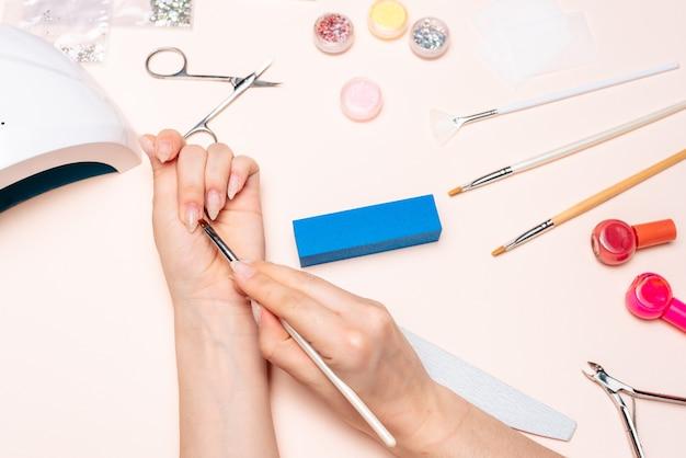 Handen van een meisje dat een manicure doet, gel met een borstel toepast. het uitzicht vanaf de top