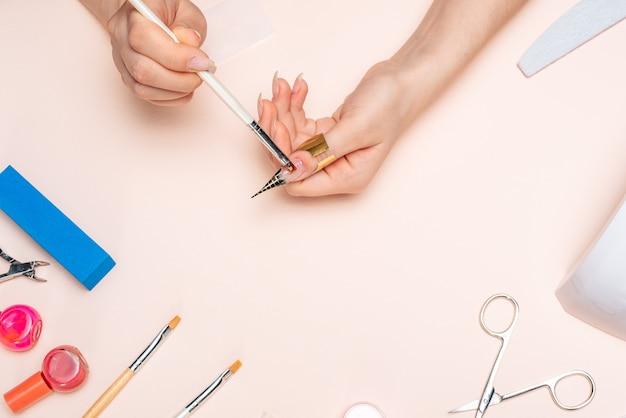 Handen van een meisje dat gel op haar nagels aanbrengt met een borstel