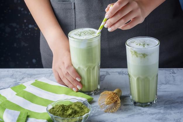 Handen van een meisje die een glas met groene latte houden. matcha groene thee en sojamelkdrank