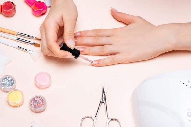 Handen van een meisje die een manicure thuis doen, handenclose-up. het uitzicht vanaf de top