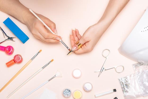 Handen van een meisje gel toe te passen op haar nagels met een borstel. het uitzicht vanaf de top