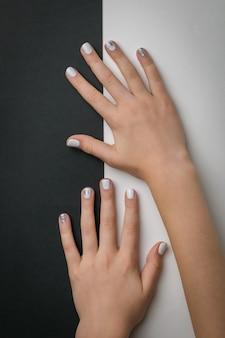 Handen van een meisje met een glanzende manicure op een wit en zwart
