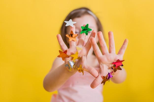 Handen van een meisje met veelkleurige confetti op handen