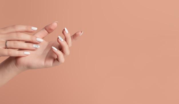 Handen van een mooie verzorgde vrouw met vrouwelijke nagels op een beige achtergrond.
