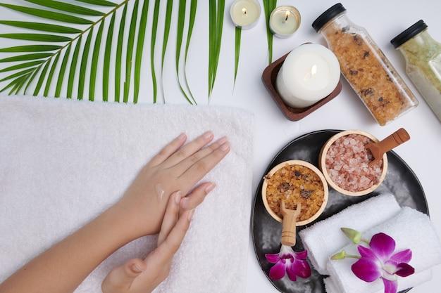 Handen van een mooie vrouw die dennen etherische olie laat vallen. spa-behandeling en product voor vrouwelijke hand spa, massage, kaarsen, ontspanning. plat leggen. bovenaanzicht.