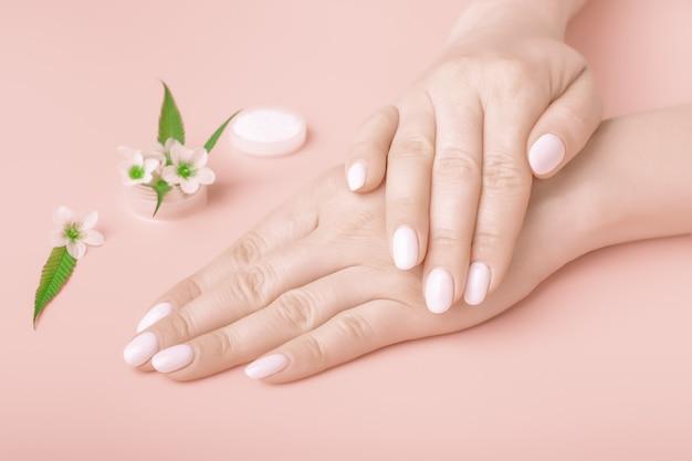 Handen van een mooie vrouw op een perzik roze achtergrond. fijne handjes met natuurlijke manicure, schone huid. witte nagels.