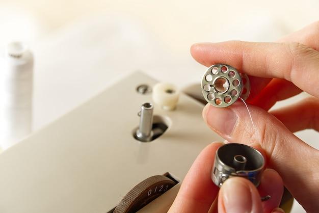 Handen van een naaister die draad van een spoel naar een klosje windt, close-up.