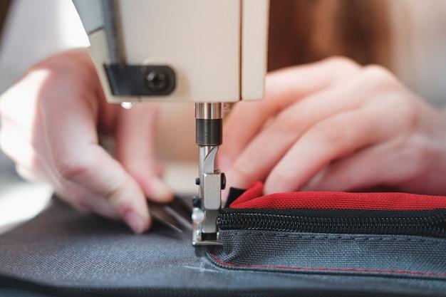 Handen van een naaister die nauwkeurig werk, close-upmening doet.