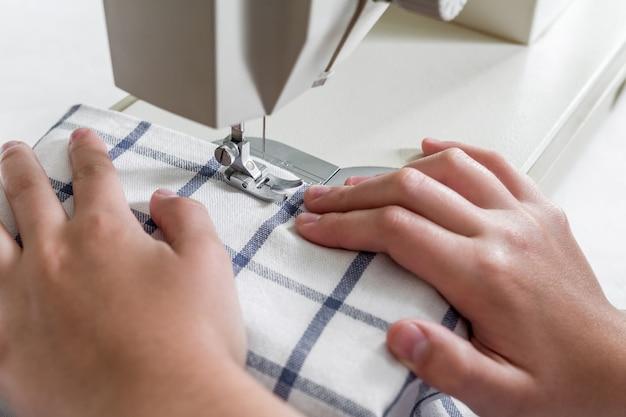Handen van een naaister op een naaimachine tijdens het naaien met een kopie van de ruimte