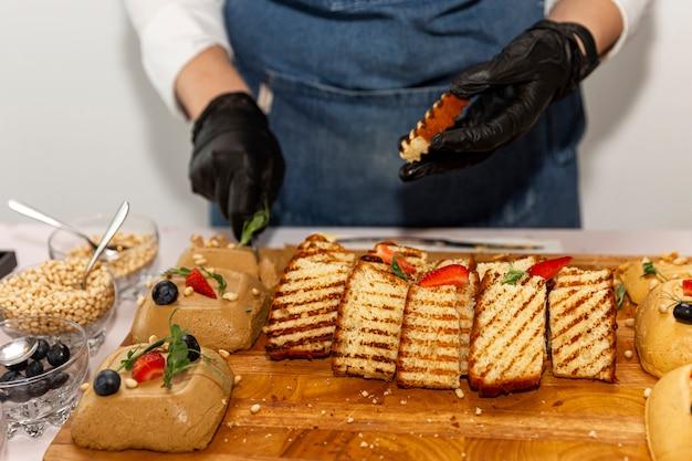 Handen van een ober in zwarte handschoenen aan de buffettafel. smakelijke snacks. detailopname.
