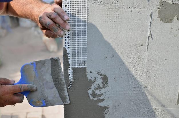 Handen van een oude handarbeider met muurbepleisteringshulpmiddelen die huis renoveren