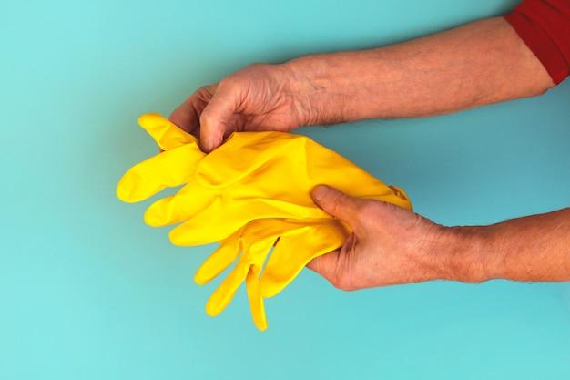 Handen van een oudere gebruinde man met gele rubberen beschermende handschoenen. zelfisolatie, quarantaine, huishoudelijk huishoudelijk werk.
