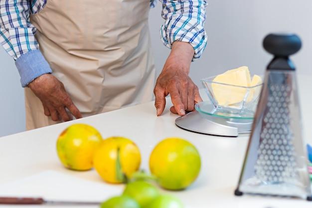 Handen van een oudere man die een weegschaal op een tafel gebruikt om boter in een keuken te wegen