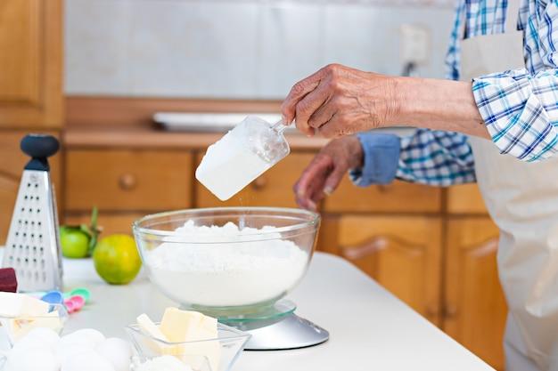 Handen van een oudere man die een weegschaal op een tafel gebruikt om meel in een keuken te wegen