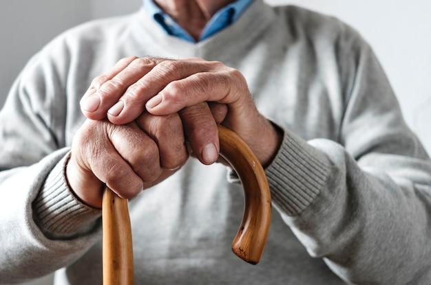 Handen van een oudere man rustend op een wandelstok