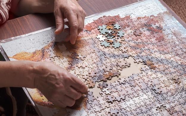 Handen van een oudere vrouw die puzzels op tafel verzamelt.