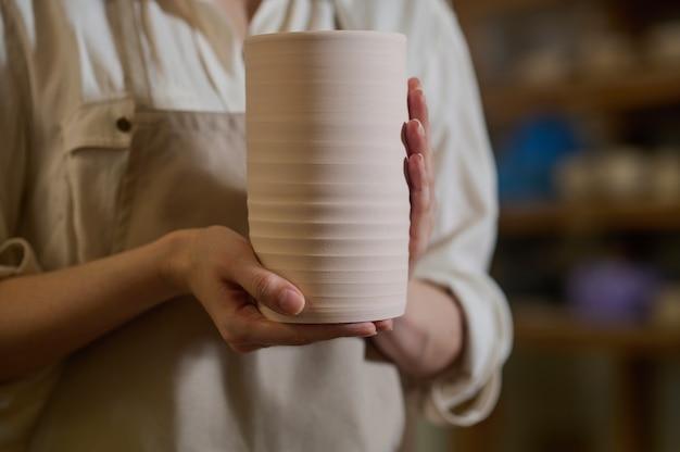 Handen van een pottenbakker met een nieuw gemaakte pot