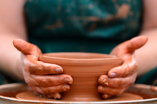 Handen van een pottenbakker. pottenbakker maken van keramische pot op de pottenbakkersschijf