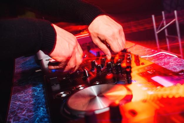 Handen van een professionele dj die muziek speelt en mengt met heldere lichteffecten