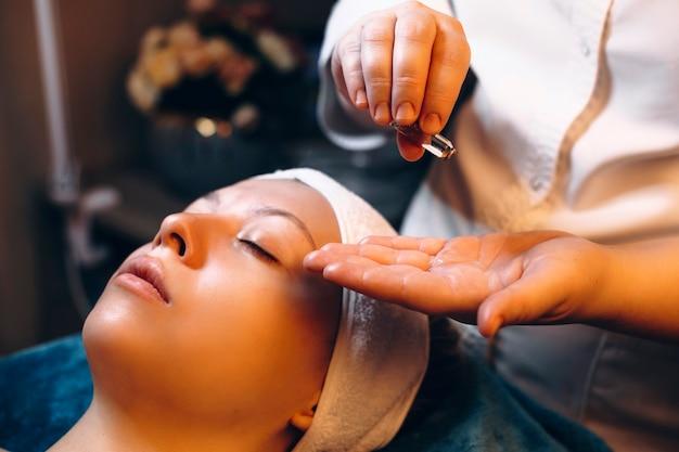 Handen van een schoonheidsspecialist die uit een ampul huidverzorgingsproduct gieten dat op een vrouwelijk gezicht zal worden toegepast.