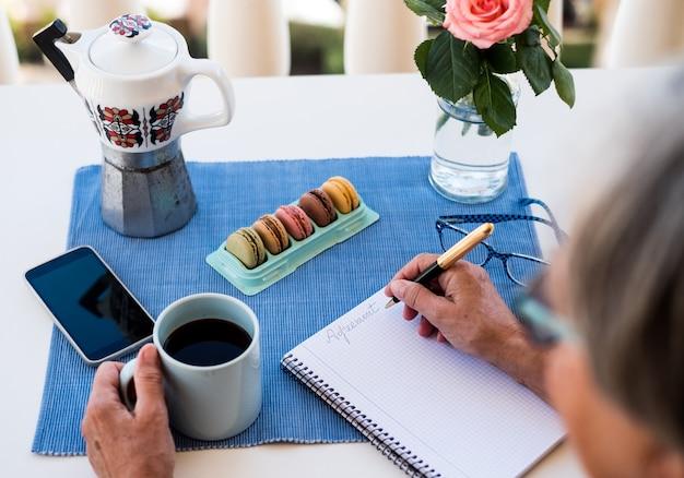 Handen van een senior vrouw die een vintage pen vasthoudt en op een vel papier schrijft. koffietijd buiten op het terras. heerlijke koekjes op tafel. mooie roze bloemen