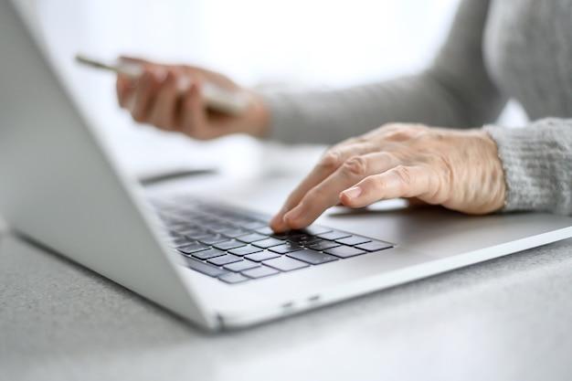 Handen van een senior vrouw werken op een laptop met een telefoon met behulp van moderne technologie in het dagelijks leven.