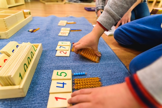 Handen van een student jongen met behulp van houten materiaal in een montessori-school.
