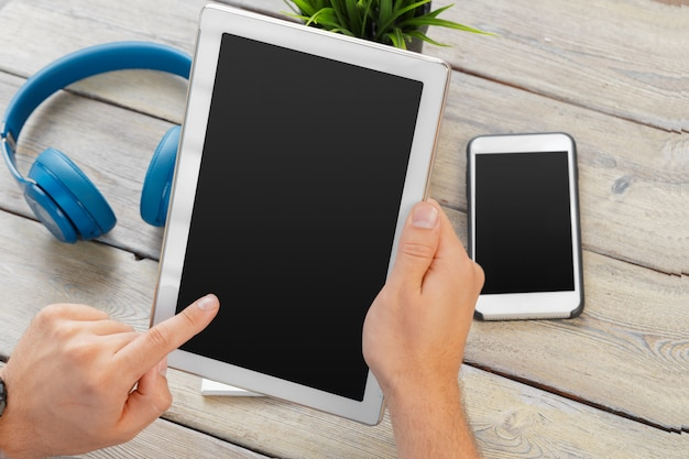 Handen van een tabletapparaat van de mensenholding over een houten werkruimtelijst