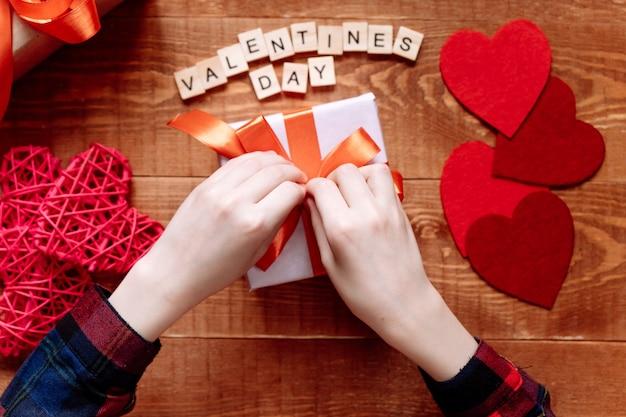 Handen van een tiener die een cadeau voorbereidt voor valentijnsdag op een houten achtergrond. harten en vakantiedecor op.