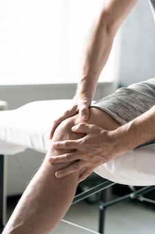 Handen van een volwassen man die zijn rechterknie masseert terwijl hij op tafel zit voor fysiotherapeutische procedures in klinieken of medische kantoren