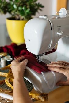 Handen van een vrouw die de maskers van het doekgezicht met naaimachine doen